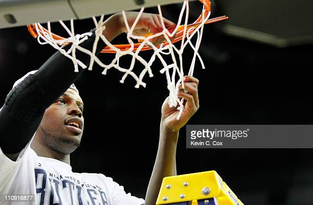 Shelvin Mack of the Butler Bulldogs celebrates defeating the Florida Gators 74 to 71 in overtime by cuttin down part of the ner during the Southeast...