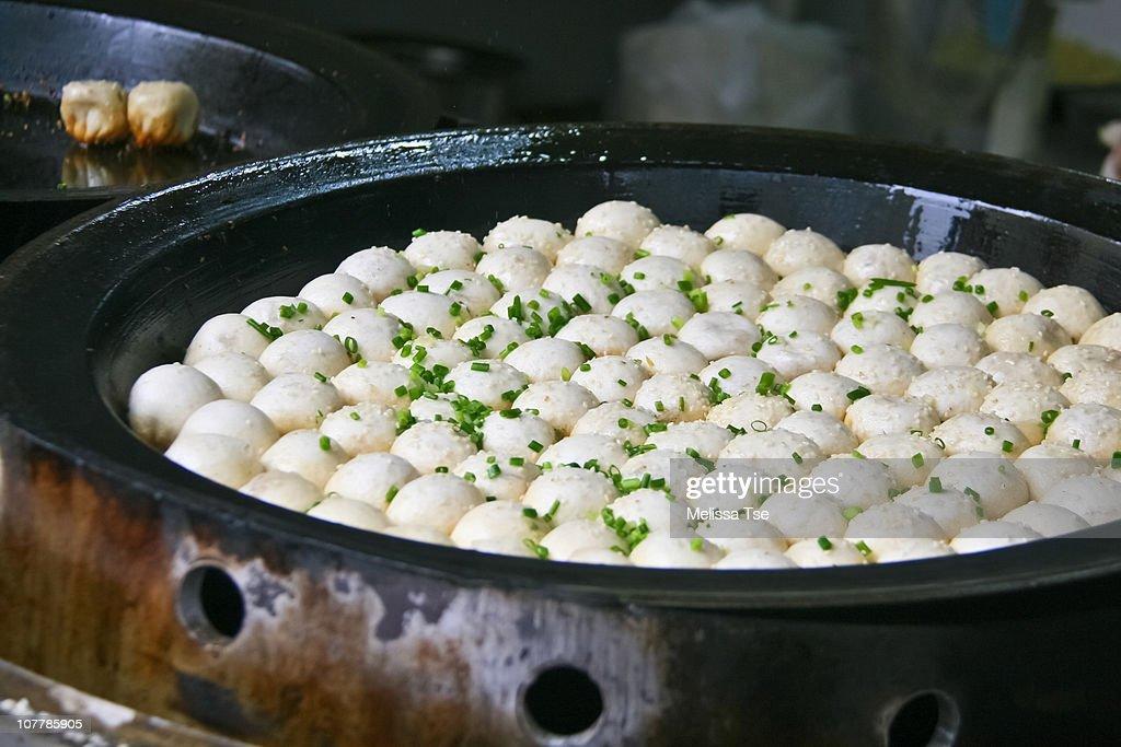 Shengjian mantou (buns) being pan-fried : Stock Photo