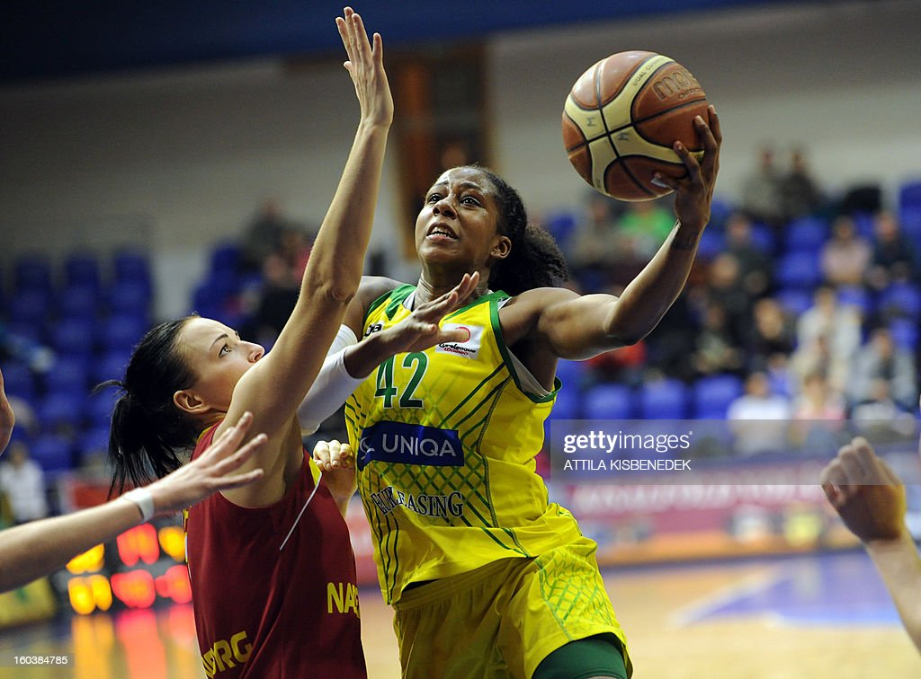 US Shenise Johnson (R) of Hungarian UE Sopron scores her basket against Elena Danlochkina (L) of Russian Nadezhda Orenburg on January 30, 2013 during their basketball EuroLeague match in Sopron, Hungary.