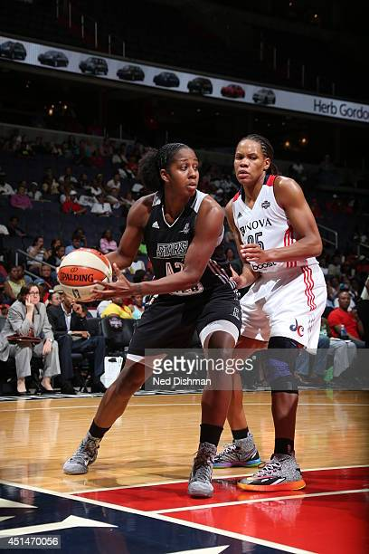 Shenise Johnson of the Washington Mystics looks to pass the ball against Monique Currie of the San Antonio Silver Stars at the Verizon Center on June...