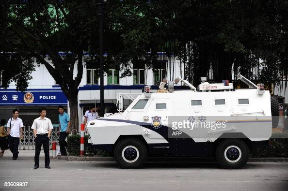 Shenzhen IN FIRST SENTENCE Pedestrians stand next to an armoured personel carrier parked outside a police station that was the center of protests...