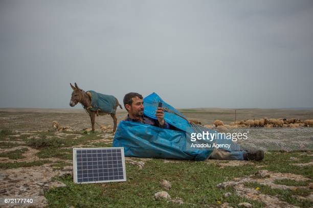 A shepherd lies near a small solar panel as he plays with his phone on grassland in the Karacadag region of Siverek district in Sanliurfa Turkey on...
