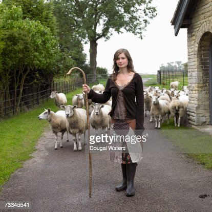 Shepherdess standing with flock and crook on country road, portrait