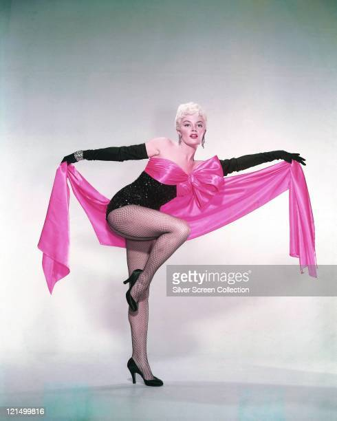 Sheree North US actress singer and dancer wearing a black leotard with fishnet stockings and long black gloves holding a length of pink fabric tied...