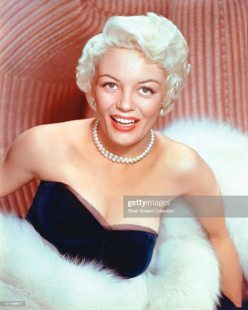 ... , and wrapped in white fur, smiling in a studio portrait, circa 1955