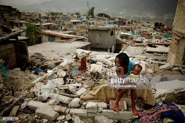 Sherider Anilus and her daughter 9monthold Monica sit on the spot where her home collapsed during last month's 70 earthquake in the Fort National...