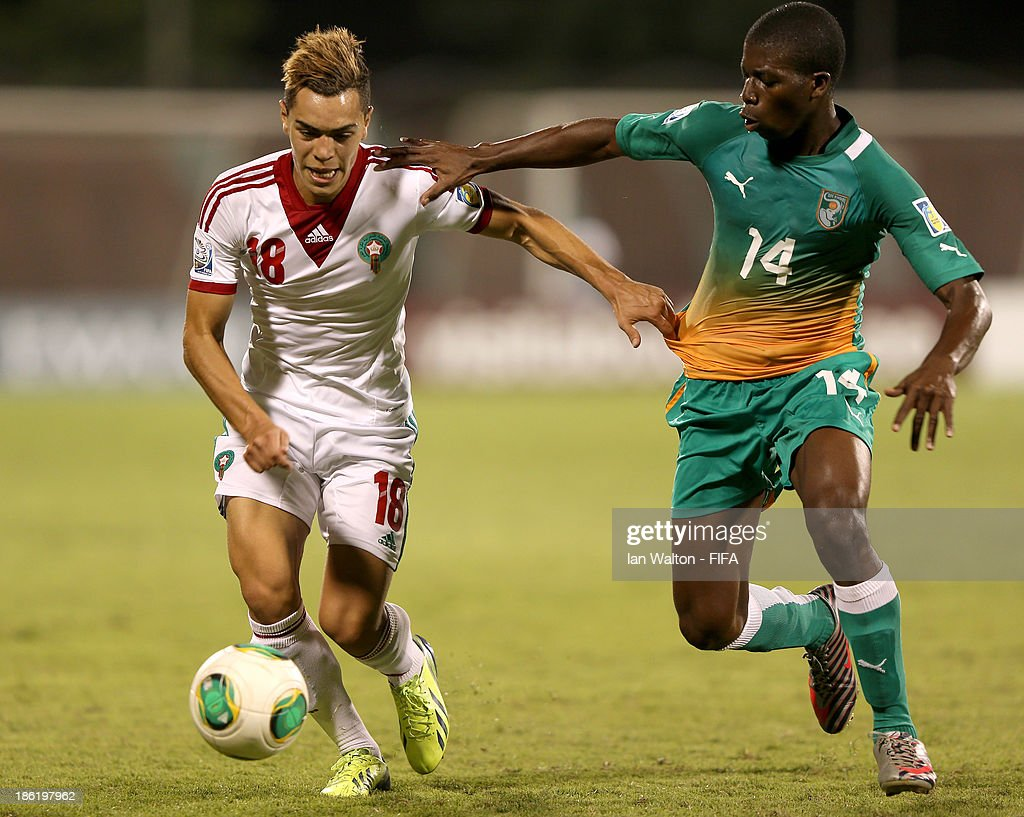Sherif Jimoh of Ivory Coast tries to tackle Hamza Sakhi of Morocco during the Round of 16 match of the FIFA U-17 World Cup between Morocco and Ivory Coast at Fujairah Stadium on October 29, 2013 in Fujairah, United Arab Emirates.