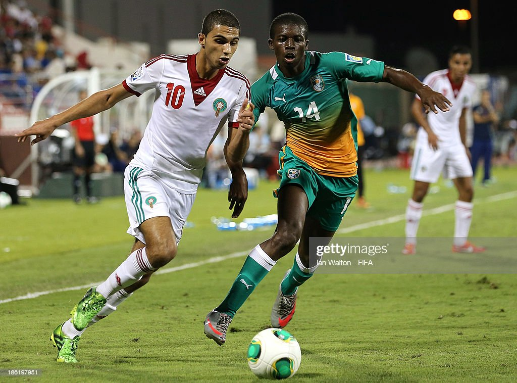 Sherif Jimoh of Ivory Coast tries to tackle Walid Sabbar of Morocco during the Round of 16 match of the FIFA U-17 World Cup between Morocco and Ivory Coast at Fujairah Stadium on October 29, 2013 in Fujairah, United Arab Emirates.