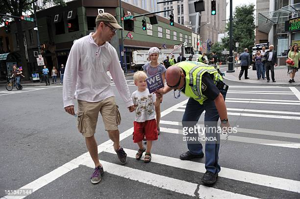 Sheriff Michael Johnson of Clayton County Georgia plays with a boy's fan as he helps a famly in a crosswalk at the corner of West 5th Street and...