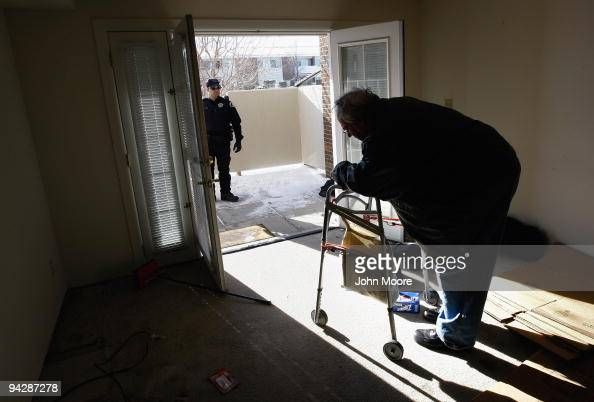 Sheriff's deputy Seth Poe waits to escort Harvey Lesser from his apartment after serving him with a court order for eviction on December 11 2009 in...