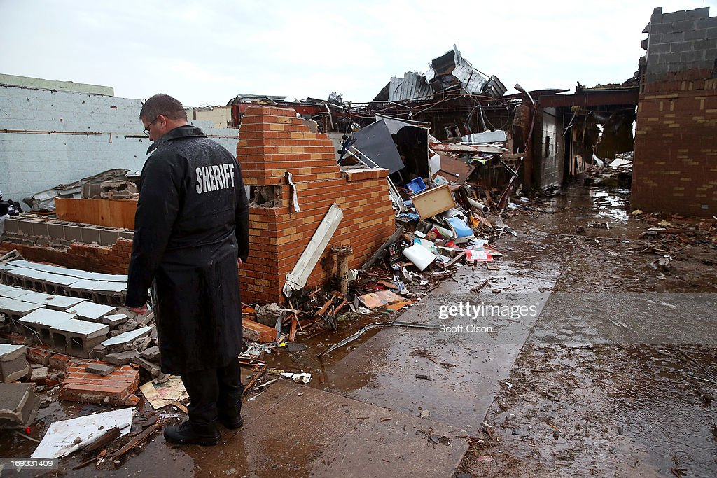 A sheriff's deputy stands among the wreckage of the Plaza Towers Elementary School after a tornado ripped through the area, on May 23, 2013 in Moore, Oklahoma. Seven children died in the school during the tornado. The two-mile-wide Category 5 tornado touched down May 20 killing at least 24 people and leaving behind extensive damage to homes and businesses. U.S. President Barack Obama promised federal aid to supplement state and local recovery efforts.