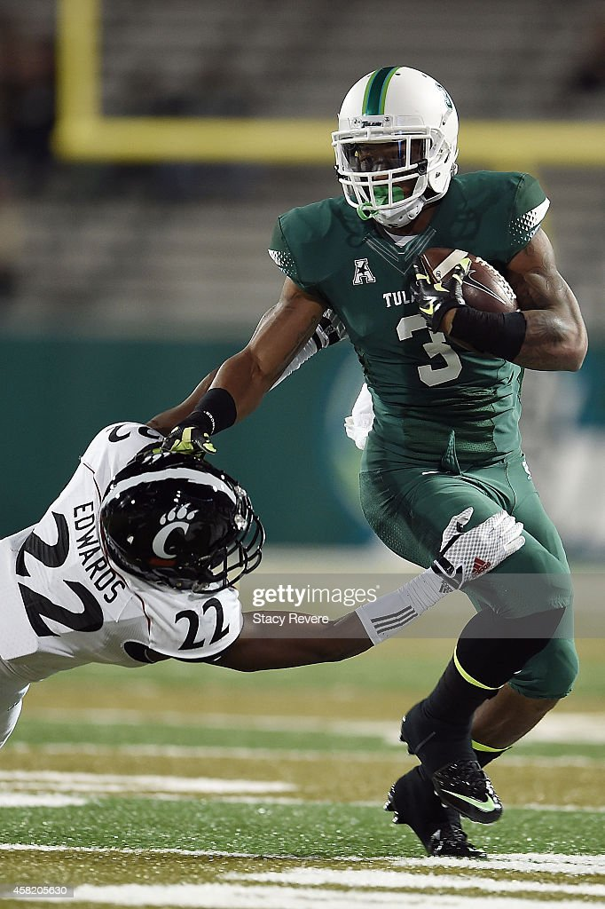 Sherman Badie #3 of the Tulane Green Wave avoids a tackle by Zach Edwards #22 of the Cincinnati Bearcats during the third quarter of a game at Yulman Stadium on October 31, 2014 in New Orleans, Louisiana.