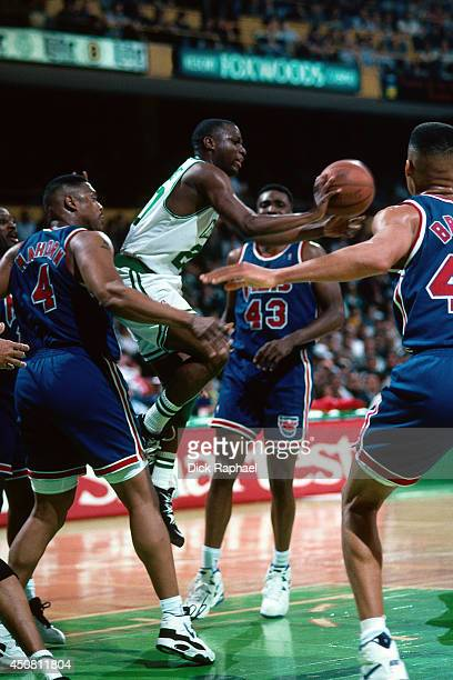 Sherman Douglas of the Boston Celtics passes the ball against Rick Mahorn of the New Jersey Nets during a game played in 1995 at the Boston Garden in...