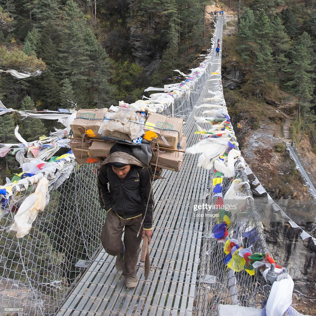 Sherpa crossing a swing bridge on the path to Everest Base Camp Himalayas Nepal