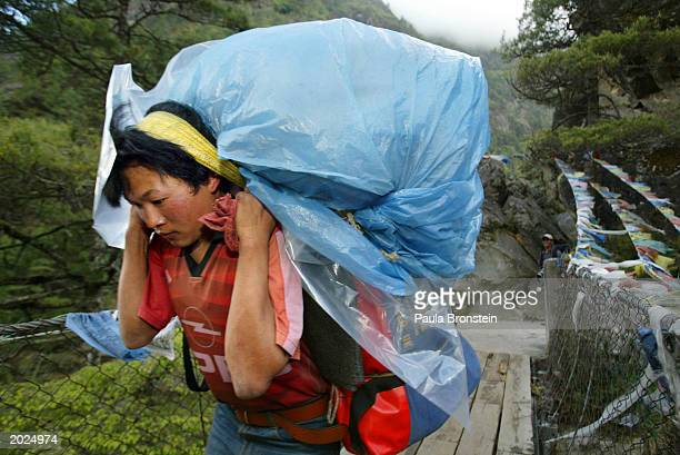 Sherpa porter carries a heavy load over a suspension bridge along the Everest trail May 23 2003 in the Solu Khumbu region of Nepal With a ceasefire...