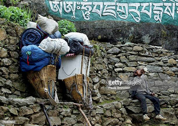 Sherpa porter rests along side his heavy load on the Everest trail May 25 2003 in the Solu Khumbu region Nepal Sherpas are paid by the kilo and are...