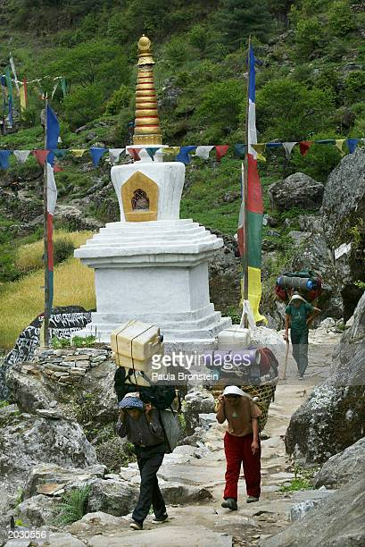 Sherpa porters carry heavy loads up the Everest trail past a Buddhist stupa and prayer flags May 25 2003 in the Solu Khumbu region Sherpas are paid...