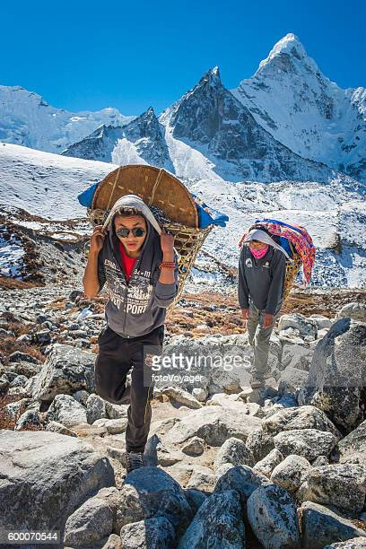 Sherpa porters carrying traditional wicker baskets below Himalaya peaks Nepal