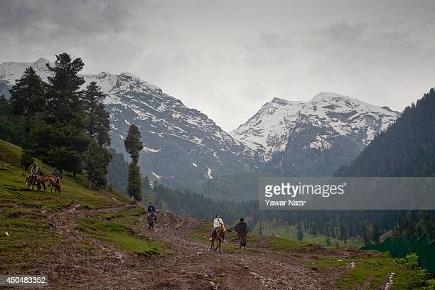 Sherpas walk with tourists on the hillside on June 12 2014 in Aru 112 Km south Srinagar the summer capital of Indian administered Kashmir India...