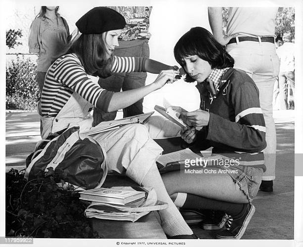 Sherry Hursey combing Didi Conn's hair while she is reading the book 'Sea gull' in a scene from the film 'Almost Summer' 1978