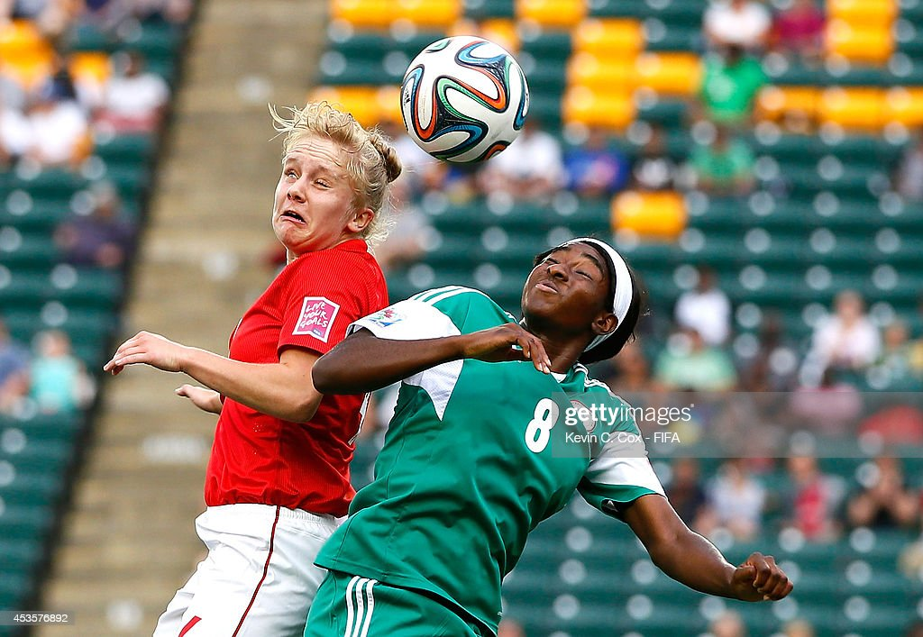 Sherry McCue of England battles for a header against Courtney Dike of Nigeria during the FIFA U-20 Women's World Cup Canada 2014 Group C match between Nigeria and England at Commonwealth Stadium on August 13, 2014 in Edmonton, Canada.