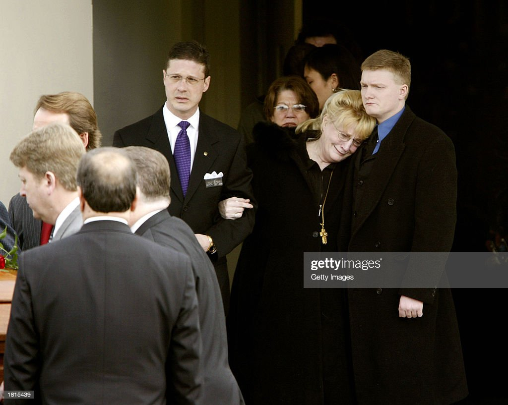 Sherry Ray (C), the wife of deceased country music singer Johnny Paycheck, is held by Paycheck's son Bo (R) February 25, 2003 at PayCheck's funeral in Nashville, Tennessee.