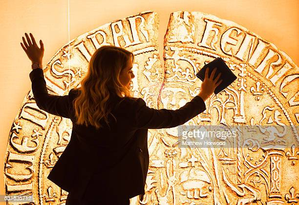 Sherry Thomas of the Royal Mint Experience cleans an image of a Henry VII sovereign coin during the opening of the Royal Mint Experience at the Royal...
