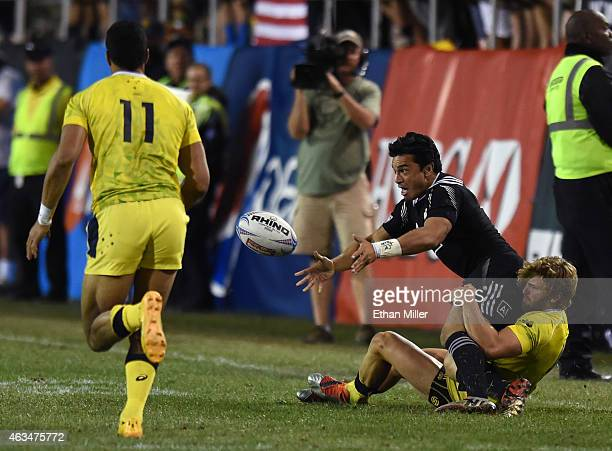 Sherwin Stowers of New Zealand passes the ball as he is brought down by Lewis Holland of Australia during the USA Sevens Rugby tournament at Sam Boyd...