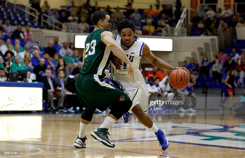 Sherwood Brown #25 of the Florida Gulf Coast University Eagles drives as Chris Perez #23 of the Stetson Hatters defends during the game at Alico Arena on January 25, 2013 in Ft. Myers, Florida.