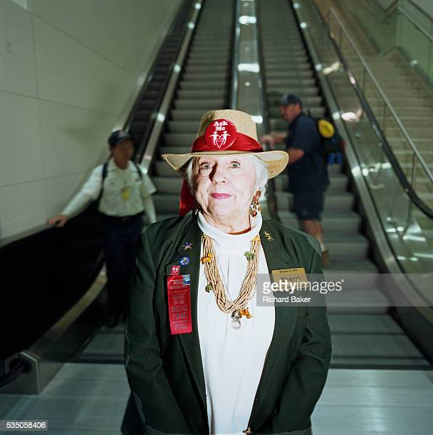 Sheryl is an Airport Ambassador Volunteer at Dallas Fort Worth Texas and stands for a portrait at the foot of some escalators in the main terminal...