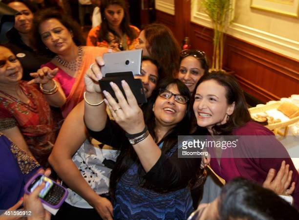 Sheryl Sandberg billionaire and chief operating officer of Facebook Inc right poses for a 'selfie' photo with with a participant during an event...