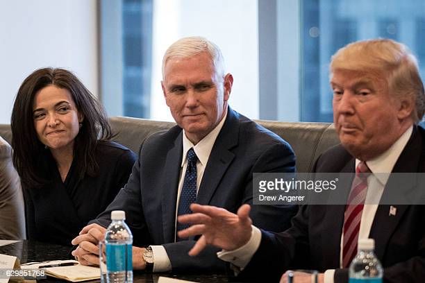 Sheryl Sandberg chief operating officer of Facebook and Vice Presidentelect Mike Pence listen as Presidentelect Donald Trump speaks during a meeting...