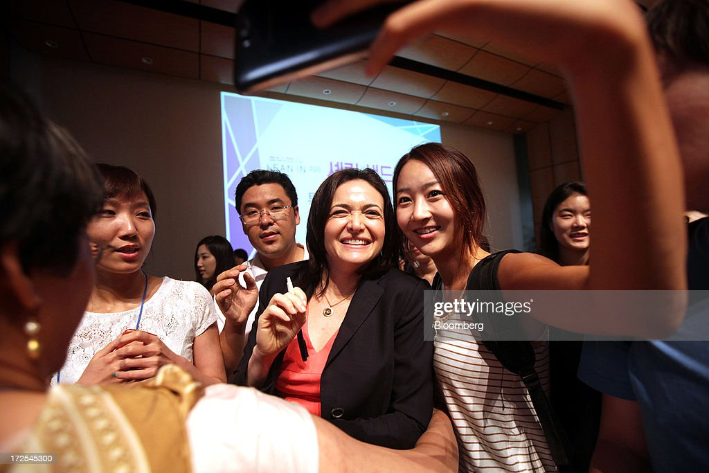 <a gi-track='captionPersonalityLinkClicked' href=/galleries/search?phrase=Sheryl+Sandberg&family=editorial&specificpeople=5922850 ng-click='$event.stopPropagation()'>Sheryl Sandberg</a>, chief operating officer of Facebook Inc., center, poses with students for photographs after her speech at Yonsei University in Seoul, South Korea, on Wednesday, July 3, 2013. Sandberg is in South Korea to promote her book 'Lean In: Women, Work, and the Will to Lead.' Photographer: Woohae Cho/Bloomberg via Getty Images