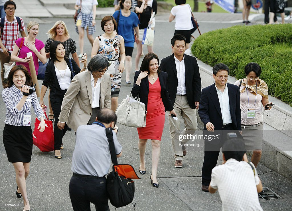 Sheryl Sandberg, chief operating officer of Facebook Inc., center, arrives to deliver a speech at Yonsei University in Seoul, South Korea, on Wednesday, July 3, 2013. Sandberg is in South Korea to promote her book 'Lean In: Women, Work, and the Will to Lead.' Photographer: Woohae Cho/Bloomberg via Getty Images