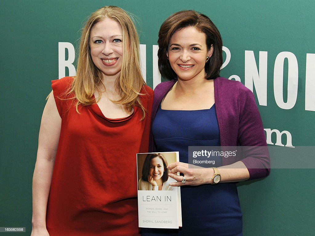 Sheryl Sandberg, chief operating officer of Facebook Inc., right, and Chelsea Clinton, daughter of former U.S. President Bill Clinton, pose for photographs with Sandberg's new book 'Lean In' at a Barnes & Noble Inc. store in New York, U.S., on Tuesday, March 12, 2013. Sandberg's book, released on March 11, advises women to get over their ambivalence about being ambitious, think big and take risks. Photographer: Peter Foley/Bloomberg via Getty Images