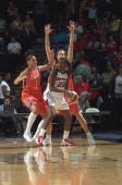 Sheryl Swoopes of the Houston Comets looks to pass while double teamed by Lisa Harrison and Anna DeForge of the Phoenix Mercury during the WNBA game...