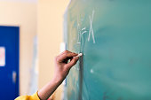 Photo of student writing a math problem or formula  on the chalkboard. Hand of a student working on math equation. Male teen hand to draw something on blackboard with chalk. Young Caucasian male child
