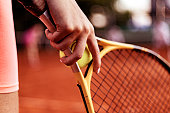 Close Up of Female Player Hand Holding Tennis Racket on Court. Cropped Shot of Woman Holding a Tennis Racket at the Court