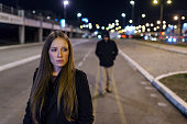 Beautiful young woman walking and being stalked by man criminal on the street at night. Dangerous situation for lonely female. Unrecognizable male figure with hidden face in hood walking, looking dang