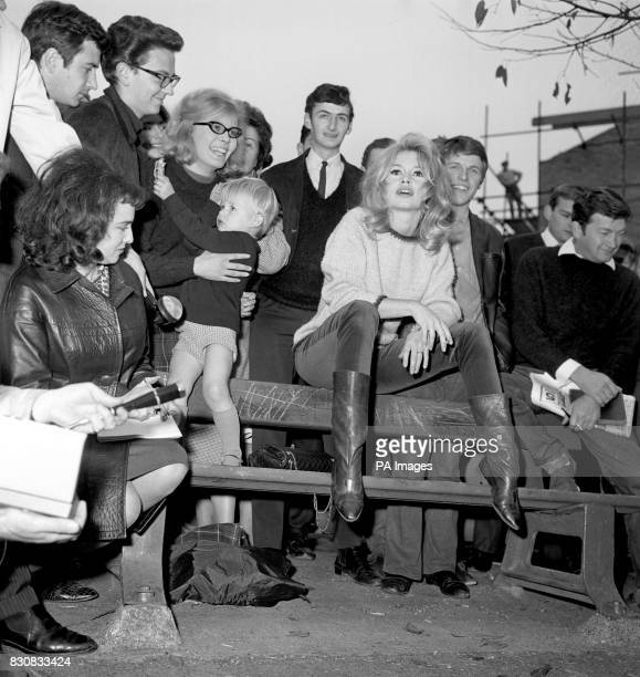 She's the girl who can't help attracting a crowd and sightseers surround French actress Brigitte Bardot as she sits on the back of a bench at...