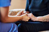 Cropped shot of a nurse holding an elderly woman's hands compassionately