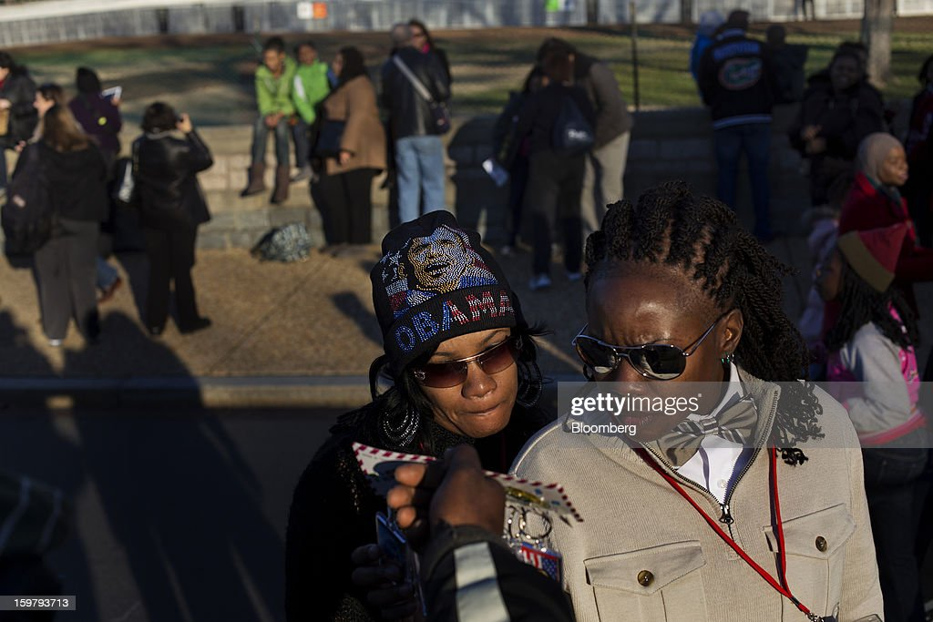 Shetakia Sims, of Dallas, Texas, left, wears an Obama hat while standing with Dee Wilson, of Shreveport, Louisiana, while buying commemorative keychains ahead of the presidential inauguration in Washington, D.C., U.S., on Sunday, Jan. 20, 2013. As he enters his second term U.S. President Barack Obama has shed the aura of a hopeful consensus builder determined to break partisan gridlock and adopted a more confrontational stance with Republicans. Photographer: Victor J. Blue/Bloomberg via Getty Images