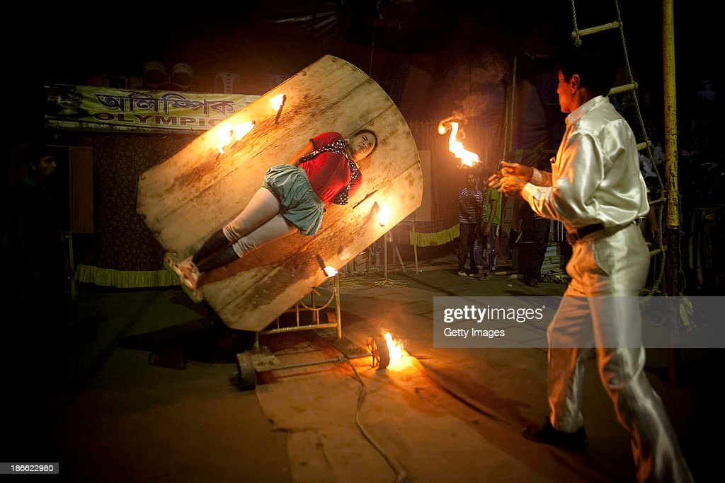 Sheuliy, shuts her eyes as Rezaul Karim throws flaming knives at her during a performance at the Olympic Circus, October 31, 2013 in Jamsha, Bangladesh. Sheuliy, who doesn't know her age, got married to another circus worker when she was 10 or 11 years old. She never had a chance to go to school. Rezaul, who is 52 years old, joined the circus when he was a teenager. He dropped out of school when he was 12 years old. Rezaul enjoys his work in the circus. He like performing and watching his friends perform, and he enjoys the music. Generations of low income families are born into circuses with rarely the hope of ever working in different profession or escaping the harsh realities of the circus. The children, often very young, are trained to be full working members usually without the opportunity for an education. As modernization slowly takes over landscape of Bangladesh, the circus is a dying art form and is moving further and further away from mainstream entertainment.