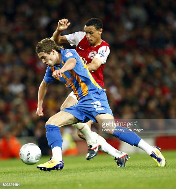 Shewsbury's Tom Bradshaw in action with Arsenal's Francis Coquelin during the Carling Cup Third Round match at the Emirates Stadium London