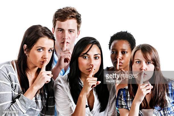 Einer Strickerei mit dem Schriftzug Shhh! Fünf junge Menschen mit Finger auf den Mund legen
