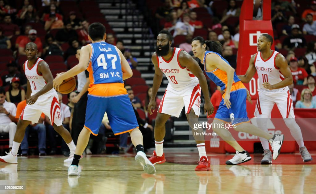Shi #47 of Shanghai Sharks controls the ball defended by James Harden #13 of Houston Rockets in the first half at Toyota Center on October 5, 2017 in Houston, Texas.