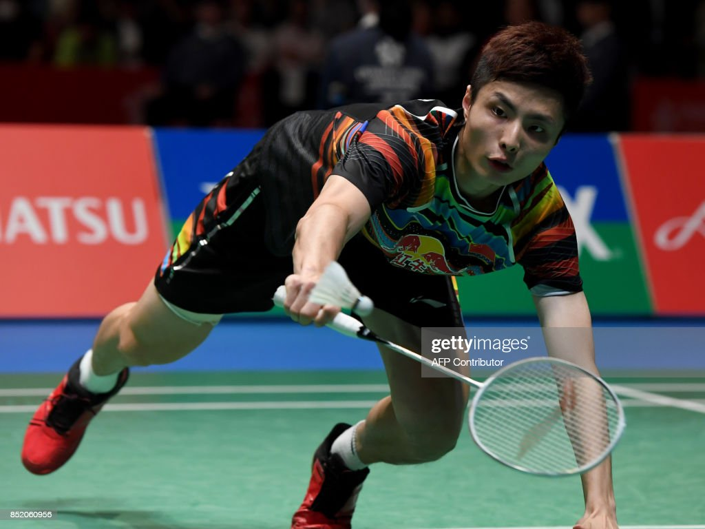 Shi Yuqi of China dives to return towards Lee Chong Wei of
