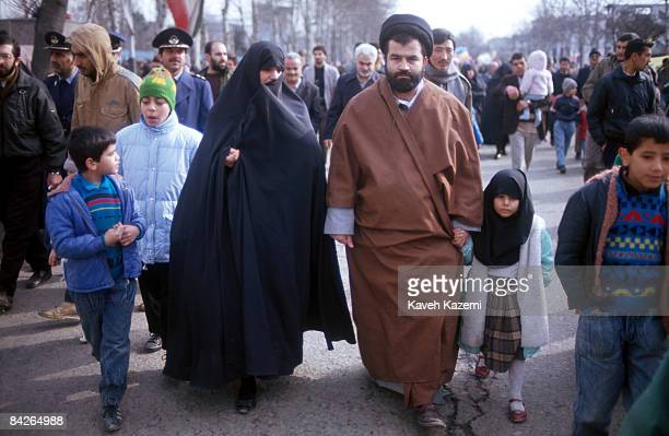 A Shia clergyman in black turban with his wife and daughter at a demonstration in Tehran on the anniversary of the Islamic Revolution 11th February...