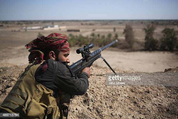 Shia militia sniper from Abo al Fadhel al Abbas provides cover for Iraqi Army troops as they assault ISIL fighters on the frontline April 14 2015...