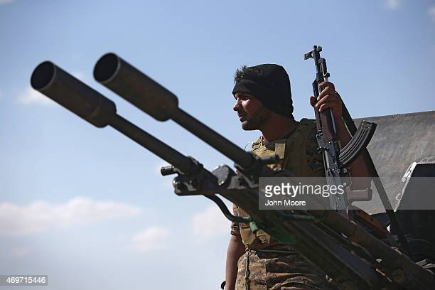 Shia militiaman from Abu al Fadhel al Abbas watches as Iraqi Army troops assault ISIL fighters on the frontline April 14 2015 near AlKarmah in Anbar...